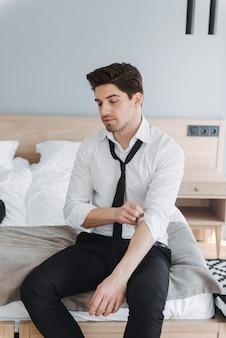 Кавказский молодой бизнесмен в строгой одежде, глядя вниз, сидя на кровати в гостиничной квартире