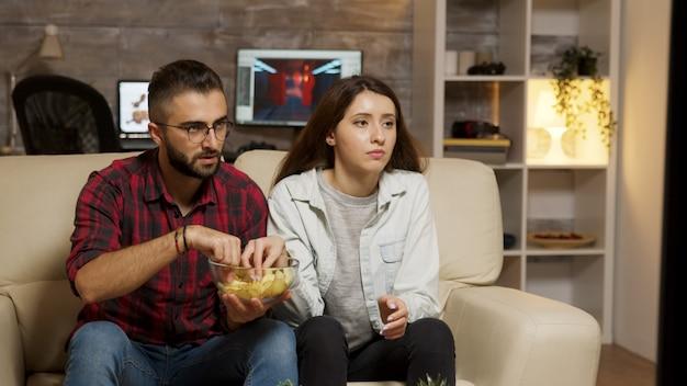 Giovani coppie caucasiche che mangiano patatine mentre si guarda la televisione. coppia in cerca preoccupata per la televisione.