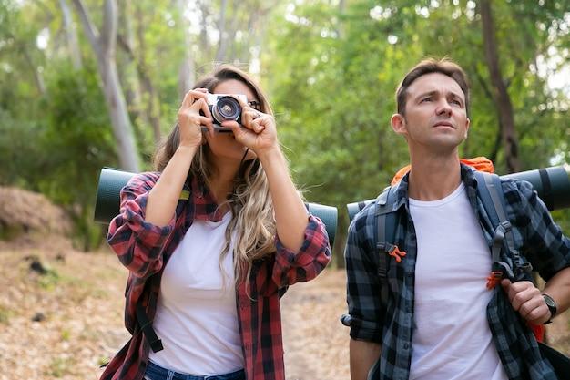Giovani coppie caucasiche che fanno un'escursione nella foresta e che prendono la foto con la macchina fotografica. riflessivo viaggiatore maschio in piedi vicino a donna e guardando il paesaggio. concetto di turismo, avventura e vacanze estive con lo zaino in spalla
