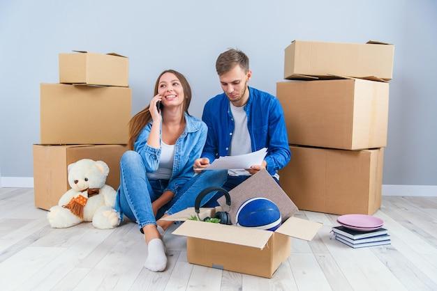 Кавказская молодая влюбленная пара сидит на паркете в собственной современной квартире и смотрит на картины с домашним дизайном интерьера.