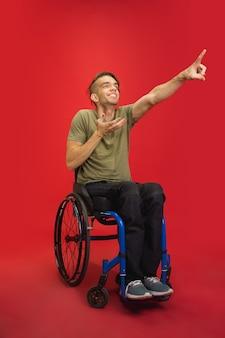 백인 젊은 장애인 남자의 초상화는 빨간색 스튜디오 배경에 격리되어 있습니다. 인간의 감정 개념