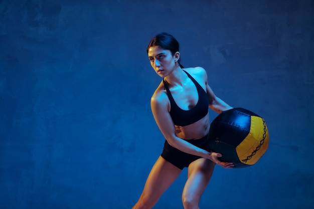 Caucasian young female athlete practicing on blue in neon light