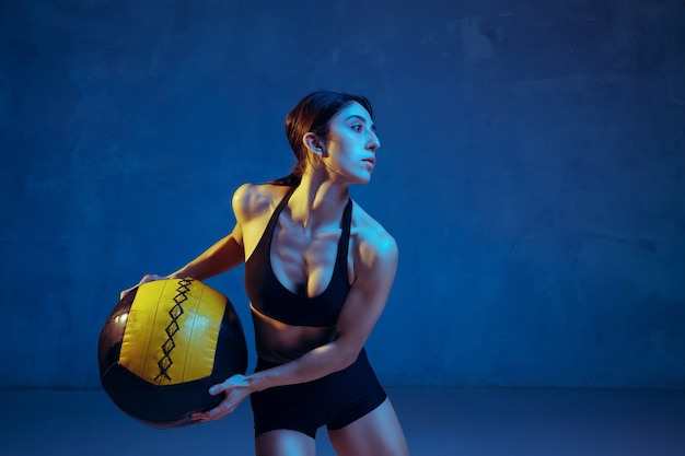네온 불빛 아래 파란색 스튜디오 배경에서 연습하는 백인 젊은 여성 운동선수