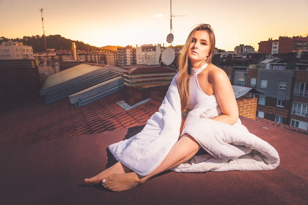Caucasian young girl enjoying the sunset on the roof