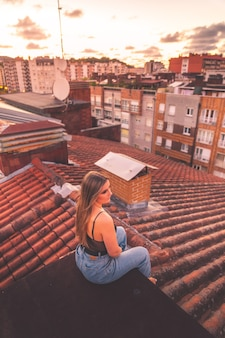 Caucasian young girl enjoying sunset with a roofview over donostia-san sebastian, basque country.
