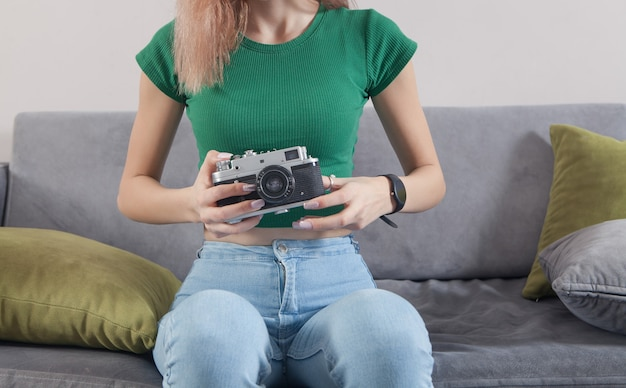 家で古いカメラを保持している白人の若い女の子。