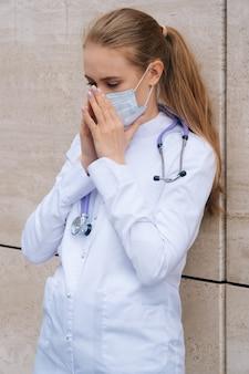 ローブの防護マスクの白人少女は通りでくしゃみをします。