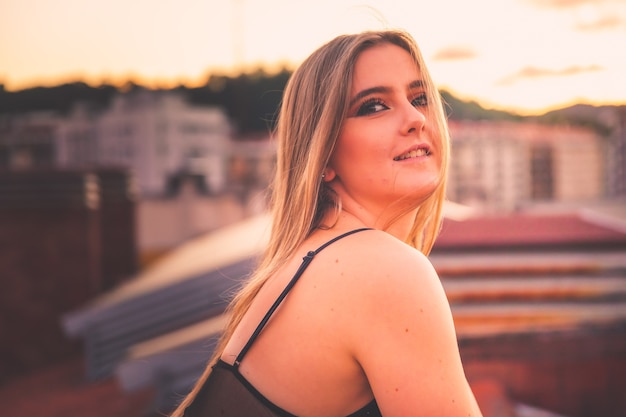 Caucasian young girl posing while sunset in a roof with a nice view over donostia-san sebastian, basque country.