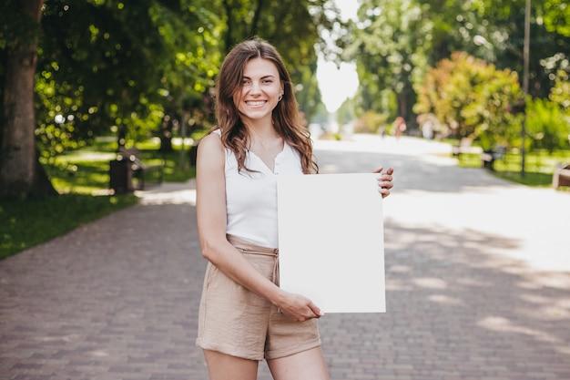 Кавказская молодая девушка студент держит плакат белой бумаги и улыбается на фоне парка