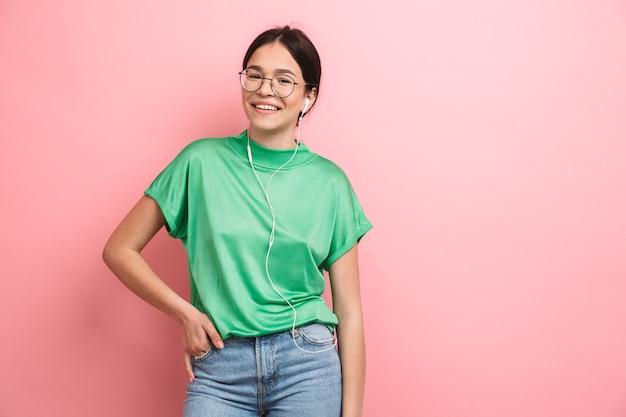 ピンクの壁に隔離されたイヤホンを使用しながら正面を見て丸い眼鏡をかけている白人の少女