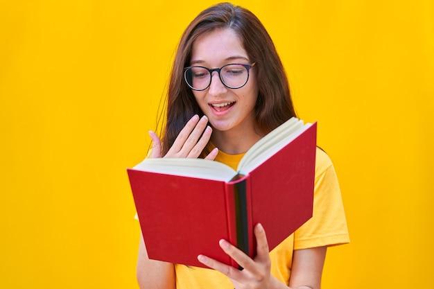 Кавказская молодая девушка с длинными темными волосами читает красную книгу с удивленным выражением лица