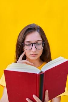 Кавказская молодая девушка с длинными волосами брюнетка читает красную книгу