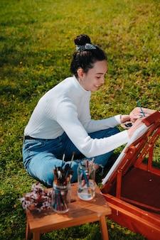 Кавказская молодая девушка с вьющимися волосами рисует холст пастельными розовыми красками, стоя на природе в парке