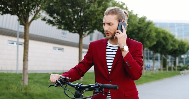 Caucasian young handsome man in red jacket standing on street at bike or electric scooter and talking on mobile phone. stylish guy speaking on cellphone outdoors. bicycle. bicyclist talk on telephone.