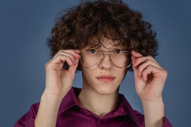 Ritratto di giovane uomo bello caucasico isolato su sfondo blu con copyspace.