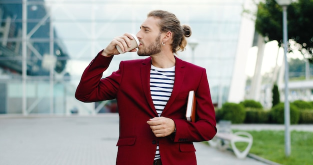 Caucasian young handsome stylish businessman walking outdoor in city with planner and sipping drink. business center modern building on background. male strolling and drinking coffee to-go.
