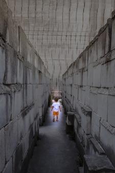 미로 관점으로 걷는 백인 어린 아이. 어린 시절의 위험한 상황에 대한 개념적 이미지입니다.