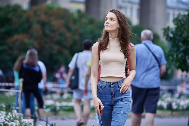 Caucasian young lady goes for walk in city at summer day