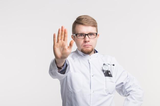 Кавказский молодой мужчина-врач с жестом остановки на белом фоне
