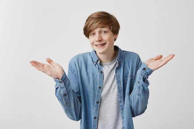 Caucasian young male has hesitant and excusing face expression, gestures doubtfully, has no answer on difficult question, being puzzled. fair-haired guy smiles with braces in confusing situation