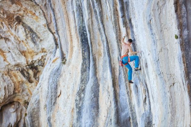 절벽에 도전 경로를 등반하는 백인 젊은 남자