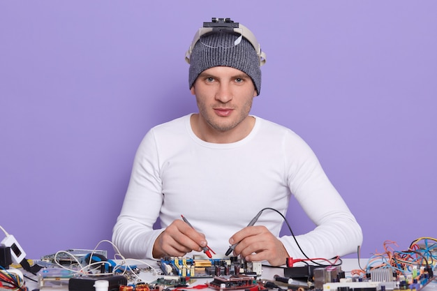 Caucasian young man dresss white shiert and gray cap, digital electronic engineer repairing computer motherboard in workshop