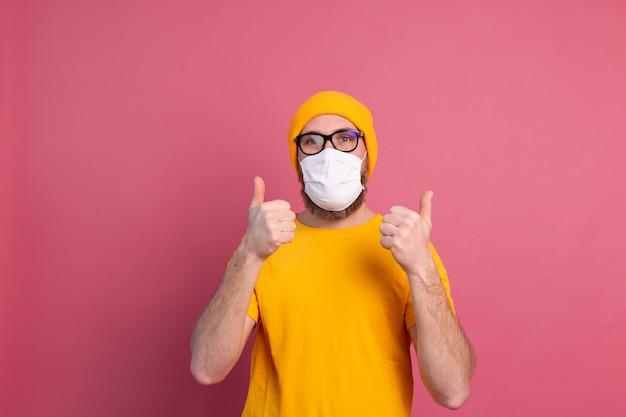 Giovane caucasico in bicchieri con maschera medica monouso per prevenire infezioni, malattie respiratorie come l'influenza