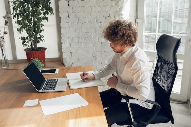 Кавказский молодой человек в деловой одежде работает в офисе онлайн-обучения