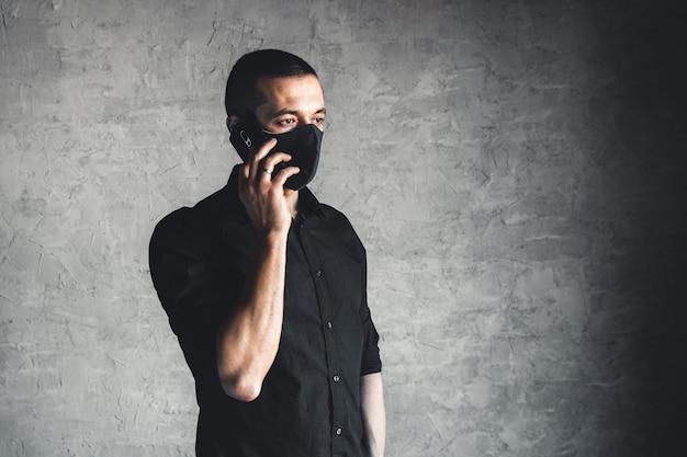 使い捨てフェイスマスクの白人の若い男。ウイルスと感染に対する保護。彼は電話をかけています