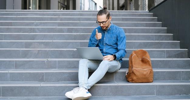 Кавказский молодой человек в очках на ступенях, открытый и разговаривает через веб-камеру на портативном компьютере. студент или фрилансер в видеочате на улице и думает. видеозвонок. отказ от большого пальца.