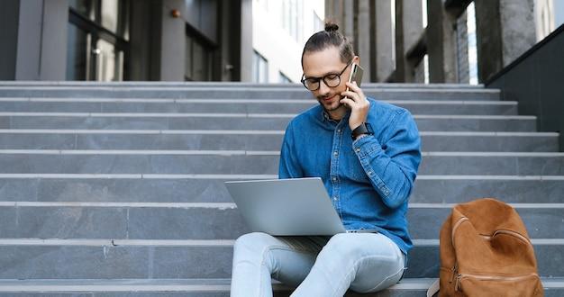 屋外の階段に座って、携帯電話で話し、ラップトップコンピューターで作業している眼鏡をかけた白人の若い男。男子学生またはフリーランサーが通りでキーボードを入力し、携帯電話で話します。