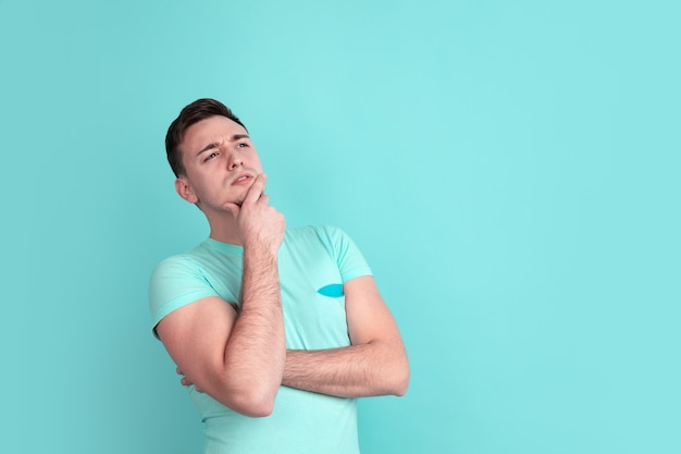 Caucasian young man portrait on blue wall