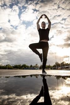 Кавказский молодой человек практикующих йогу, стоя на одной ноге, руки в стороны. утренняя тренировка на свежем воздухе после дождя. спорт и здоровый образ жизни, копирование пространства