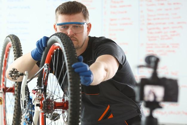 Caucasian young man repairing bicycle at workshop.