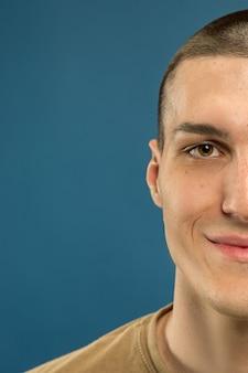 Кавказский молодой человек крупным планом выстрелил на синем фоне студии. красивая мужская модель в рубашке. концепция человеческих эмоций, выражения лица, продаж, рекламы. улыбается, выглядит счастливым.
