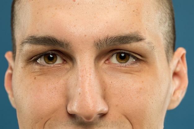青いスタジオの背景に白人の若い男のクローズアップショット。手入れの行き届いた肌の美しいモデル。人間の感情、顔の表情、男性の美しさとヘルスケアの概念。目は落ち着き、眉毛。