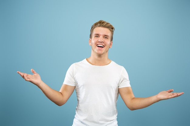 Caucasian young man's half-length portrait on blue studio background. beautiful male model in shirt. concept of human emotions, facial expression, sales, ad. pointing and showing something.
