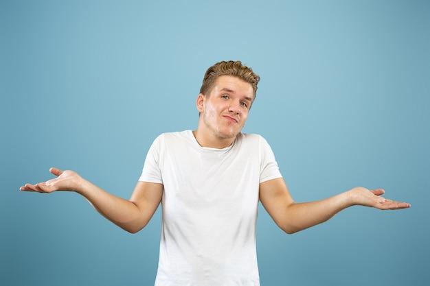 Ritratto a mezzo busto del giovane caucasico su sfondo blu studio. bellissimo modello maschile in camicia. concetto di emozioni umane, espressione facciale, vendite, annuncio. mostrando, sembra incerto, copyspace.