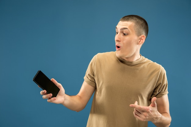 Caucasian young man's half-length portrait on blue studio background. beautiful male model in shirt. concept of human emotions, facial expression, sales, ad. showing phone screen, looks astonished.