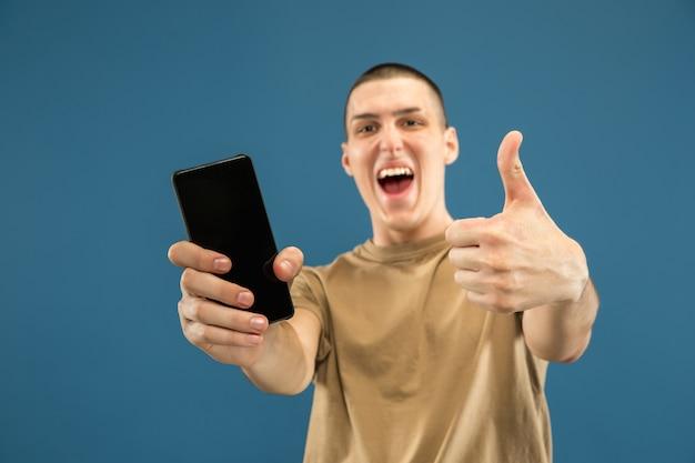 Ritratto a mezzo busto del giovane caucasico su sfondo blu studio. bellissimo modello maschile in camicia. concetto di emozioni umane, espressione facciale, vendite, annuncio. mostrando lo schermo del telefono, sembra stupito.