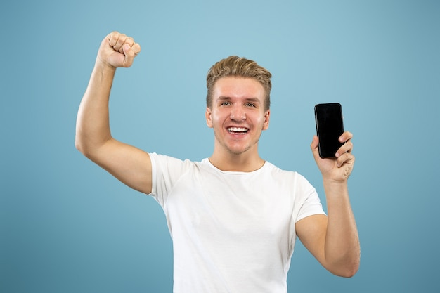 Ritratto a mezzo busto del giovane caucasico su sfondo blu studio. bellissimo modello maschile in camicia. concetto di emozioni umane, espressione facciale, vendite, annuncio. visualizzazione dello schermo del telefono, pagamento, scommesse.
