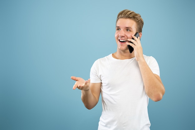 Caucasian young man's half-length portrait on blue studio background. beautiful male model in shirt. concept of human emotions, facial expression, sales, ad. talking on phone, looks happy.