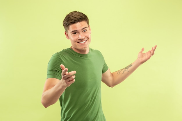 Ritratto a mezzo busto del giovane caucasico su spazio verde. bellissimo modello maschile in camicia