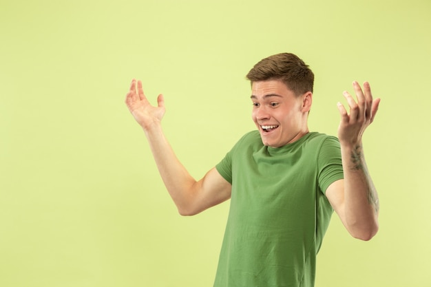 Caucasian young man's half-length portrait on green studio background. beautiful male model in shirt. concept of human emotions, facial expression, sales, ad. astonished, shocked, wondered.