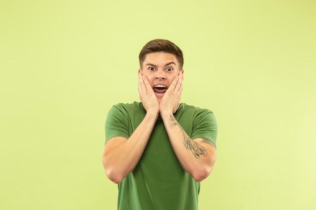 Ritratto a mezzo busto del giovane caucasico su sfondo verde studio. bellissimo modello maschile in camicia. concetto di emozioni umane, espressione facciale, vendite, annuncio. pazzo felice, in festa, scioccato.