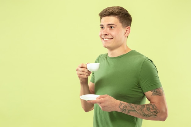 Caucasian young man's half-length portrait on green studio background. beautiful male model in shirt. concept of human emotions, facial expression, sales, ad. enjoying drinking coffee or tea.
