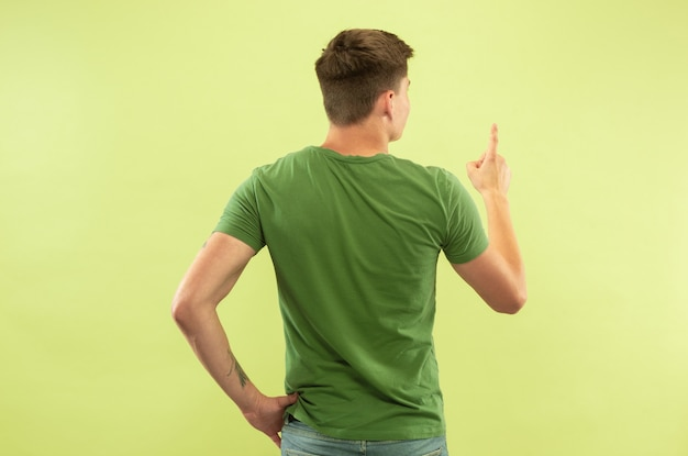 Caucasian young man's half-length portrait on green studio background. beautiful male model in shirt. concept of human emotions, facial expression, sales, ad. showing and pointing something.