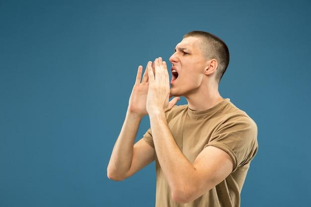 Поясный портрет кавказского молодого человека на синем фоне студии. красивая мужская модель в рубашке. концепция человеческих эмоций, выражения лица, продаж, рекламы. звонит кому-то, кричит.