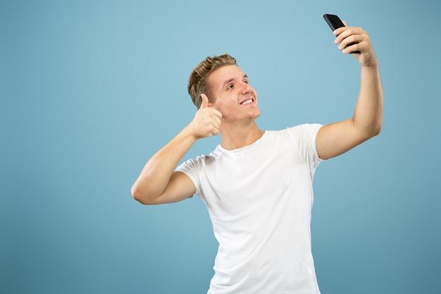 Поясный портрет кавказского молодого человека на синем фоне студии. красивая мужская модель в рубашке. концепция человеческих эмоций, выражения лица, продаж, рекламы. делаем селфи или контент для видеоблога.