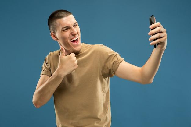 青いスタジオの背景に白人の若い男の半分の長さの肖像画。シャツの美しい男性モデル。人間の感情、表情、販売、広告の概念。 vlog用の自分撮りやビデオを作る。